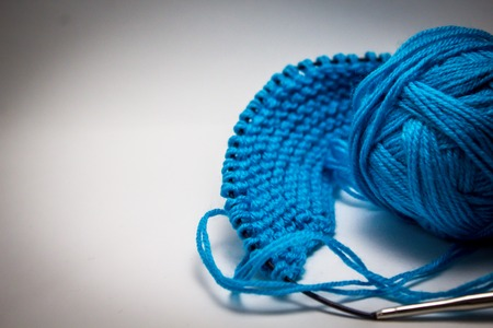 A ball of blue yarn on a white background with knitting needles for needlework Archivio Fotografico