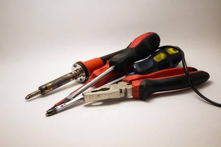 Screwdrivers, pasatizhi, soldering iron in the hands of
