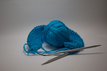 A ball of blue yarn on a white background with knitting needles for needlework