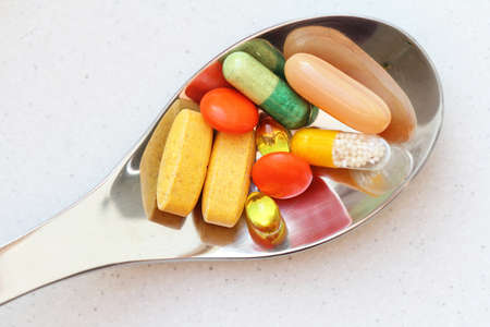 colorful pills on spoon isolated photo