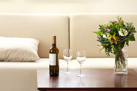 bottle of wine and glasses in living room Stock Photo