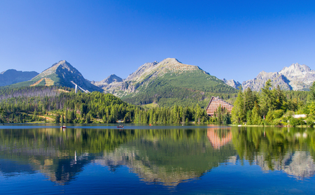 summer lake scenery landscape in high tatras with reflections on the water and high mountain range in background