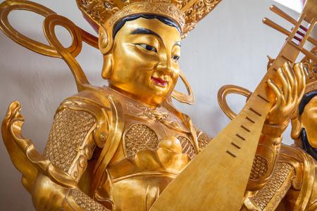 thai musical instrument: golden buddha statue playing sitar Stock Photo