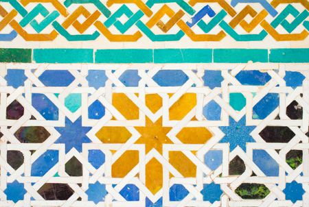 colorful ornate pattern of moorish tile decorations on alhambra wall in andalusia