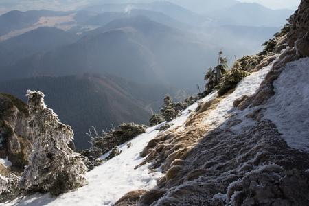 Steile beboste besneeuwde alpine helling met uitzicht op een vergezicht van bergtoppen en valleien beneden in een schilderachtig winterlandschap Stockfoto