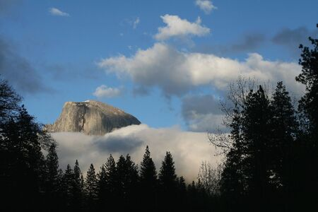 sentinel: Half Dome visible among the clouds from Sentinel Bridge in Yosemite NP Stock Photo