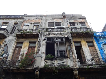 damaged: Damaged facade, windows and balconies with or without laundry, typical street scene in Old Havana, Cuba.