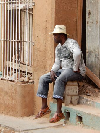 footstool: Trinidad, Cuba - January 30, 2016: A thoughtful young cuban man sitting on the footstool on the stair in a cobbled street in Trinidad, Cuba Editorial