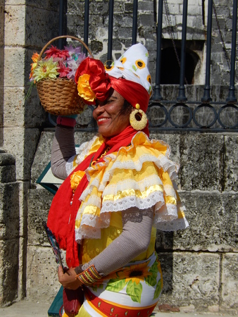 Havana, Cuba - January 19, 2016: A smiling cuban woman dressed in traditional colorful dress posing for tourists in front of the Royal Force Castle in Old Havana, Cuba.