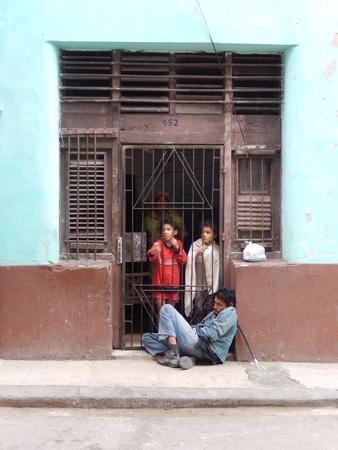 beggar's: Havana, Cuba - January 19, 2016: Two little girls begging through the security door gate in a street in Old Havana, Cuba. Editorial
