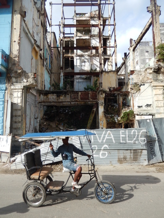 rebellion: Havana, Cuba - January 19, 2016: Taxi rickshaw driver passing by the ruins of a building and the metal fence with an inscription of 26th of July, the Day of the National Rebellion in Cuba.