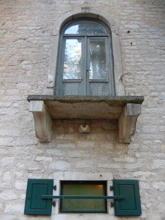 balcony door: Old door and balcony without fence on a stone facade on Brijuni, Croatia.