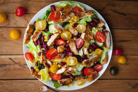 Close-up of chicken salad with fresh vegetables in a plate, on wooden background, top view