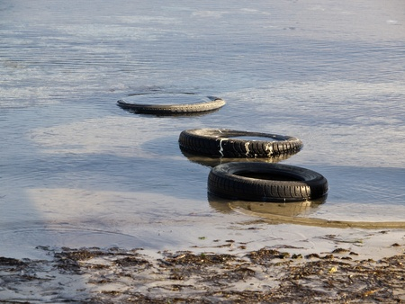polution: tyres in the water on the coast of the sea