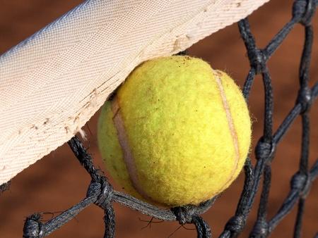 tennis ball stuck in the net Stock Photo - 12622360