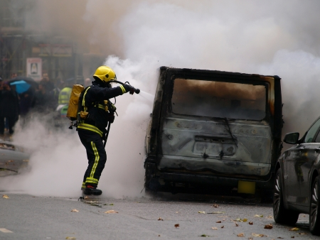 fireman fighting with the fire on the burning van Stock Photo