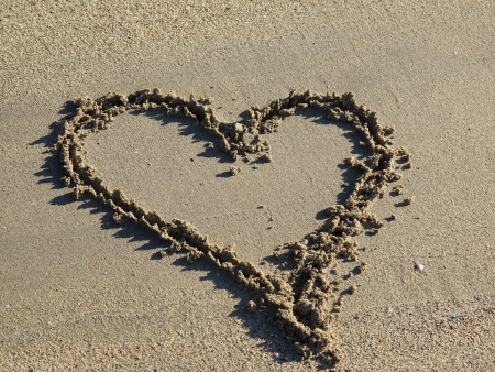 evoke: A heart shape drawn in the sand Stock Photo