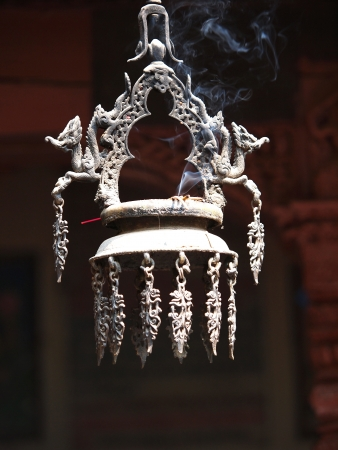 smoking incense on a bell in the buddhist temple        photo