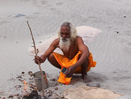 sadhu: sadhu on the send beach of ganges  cooking dinner