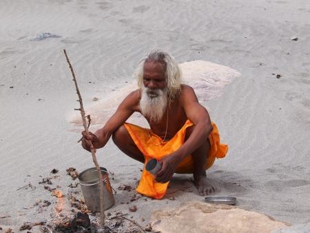 sadhu op de verzendknop strand van Ganges eten koken