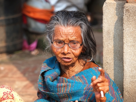 very old woman smoking cigarette         Standard-Bild