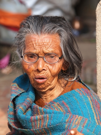 old beggar: very old woman on the street in blue dress       Stock Photo