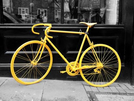 b & w photo de vieux vélo jaune sur la fenêtre de la boutique de café