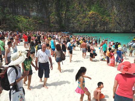 MAYA BAY, THAILAND - FEBRUARY, 2015: Crowds of visitors enjoy a day trip at Maya Bay, one of the iconic beaches of  Phi Phi  islands of Southern Thailand. Editorial