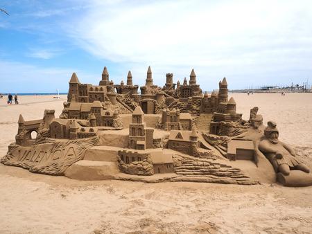 A lavish and large sand castle on an empty beach.