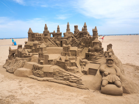 lavish: A lavish and large sand castle on an empty beach.
