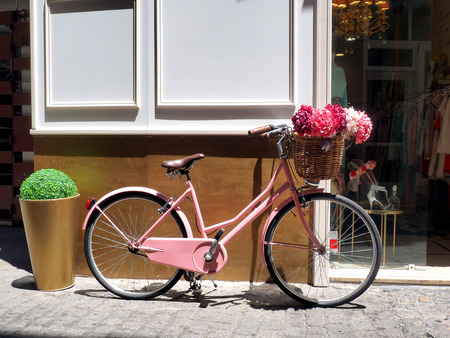 pink bike: This vintage pink girls bicycle has beautiful pink flowers in a basket on the front of the bike Stock Photo