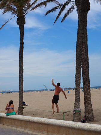 slack: VALENCIA, SPAIN - MAY 24, 2015: Unidentified young man balancing on slackline at a beach in Valenciai.