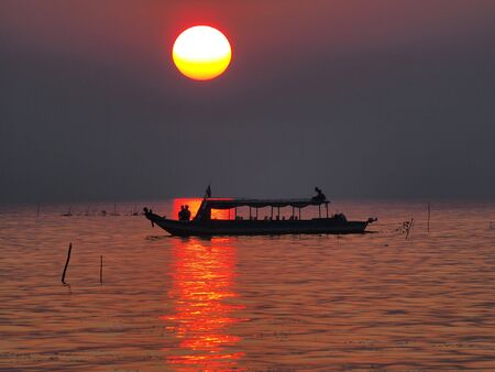 house float on water: Sunset on floating, fishing village on the lake in Cambodia Stock Photo