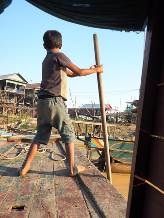 cambodian: poor cambodian boy working on a boat in floating village