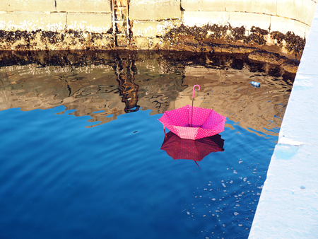 Pink spoted upturned umbrella floating on water surface