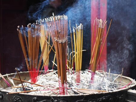temple burn: incense sticks at The Temple of the Jade Mountain  in Hanoi, Vietnam. Incense is aromatic biotic material which releases fragrant smoke when burned.