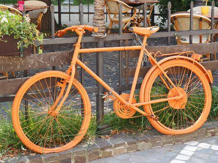 blackwhite: photo of old orange bike on the fence of the coffee shop