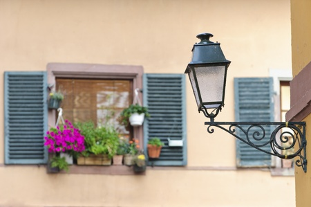 old street lamps with windows and flawers in the background photo