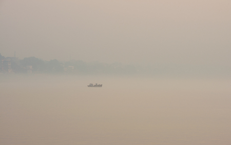 boatman: Isolated boat at sunrise over Ganges river bank near holy Varanasi city in India