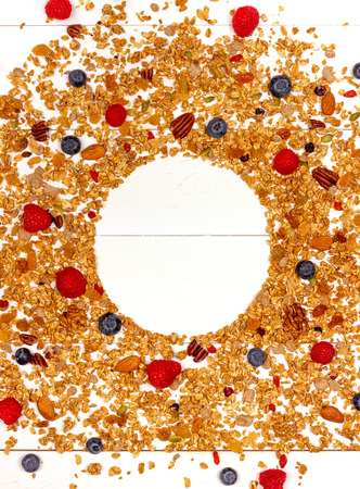 Scattered granola, nuts and berries on white wood background. 스톡 콘텐츠 - 111273629
