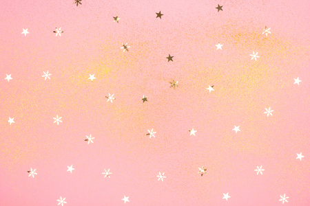 Beautiful light pink background with golden glitter and star shaped confrtti. Holiday decoration concept.