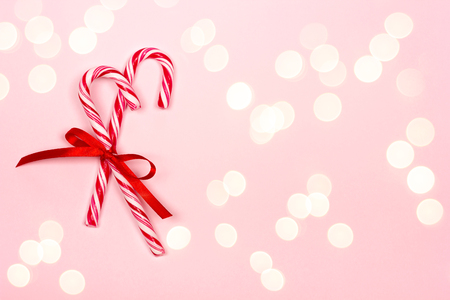 Festive Christmas background with two candy canes and ribbon on pastel pink background. Place for text.