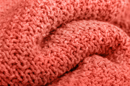 Knitted fabric texture living corel color. Selective focus. Trendy concept color of the year.