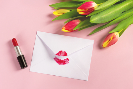 Valentines day background. Love letter concept. White envelope with red lipstick kiss and bouquet of tulips on pink pastel.