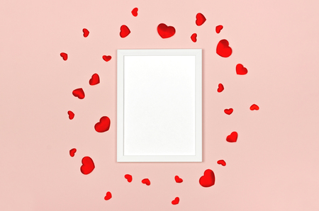 Festive background for Valentines day with blank white photo frame on pink with red hearts. Mock up for photo or text. Top view. Flat lay style.