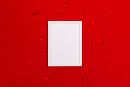 Festive background for Valentines day with blank white photo frame on red with red hearts. Mock up for photo or text. Top view. Flat lay style. Stock Photo