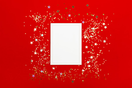 Festive background with blank white photo frame on red with scattered confetti. Mock up for photo or text. Top view. Flat lay style. Stock Photo