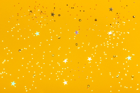 Beautiful festive yellow background with confetti. Top view. Copy space for design. Stock Photo