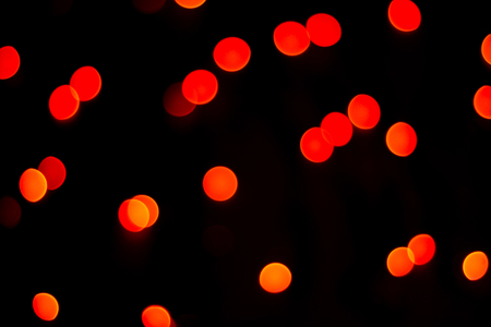 Abstract red bokeh texture on black background. Defocused sparkles.