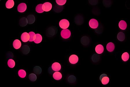 Abstract magenta bokeh texture on black background. Defocused sparkles.